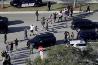 FILE - In this Feb. 14, 2018 file photo, students hold their hands in the air as they are evacuated by police from Marjory Stoneman Douglas High School in Parkland, Fla., after a shooter opened fire on the campus. Sorrow is reverberating across the country Sunday, Feb. 14, 2021, as Americans joined a Florida community in remembering the 17 lives lost three years ago in the Parkland school shooting massacre. President Joe Biden used the the occasion to call on Congress to strengthen gun laws, including requiring background checks on all gun sales and banning assault weapons (Mike Stocker/South Florida Sun-Sentinel via AP, File)