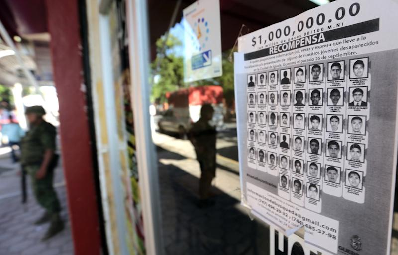A poster with the portraits of missing students is on display at the entrance of a store in Iguala, Guerrero State, Mexico, on October 7, 2014 (AFP Photo/Pedro Pardo)