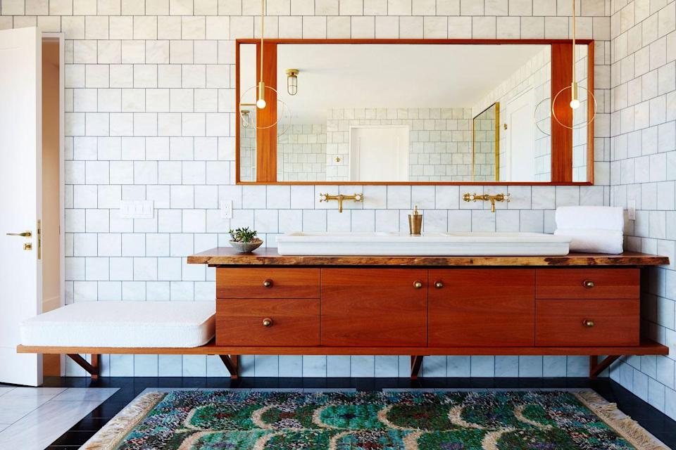 """<p>A little bit modern, a little bit industrial—we're all about this warm, light-filled bathroom designed by <a href=""""http://www.blacklacquerdesign.com/interiors/"""" rel=""""nofollow noopener"""" target=""""_blank"""" data-ylk=""""slk:Black Lacquer Design"""" class=""""link rapid-noclick-resp"""">Black Lacquer Design</a>. For added texture and color, bring in plush area rug, like this one. </p>"""