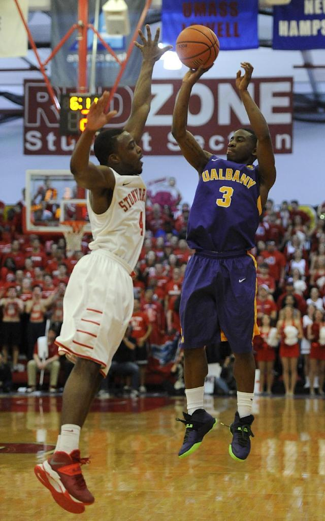 Albany's DJ Evans (3) shoots over Stony Brook' Anthony Jackson (4) during the firsthalf of an NCAA college basketball game in the championship of the America East Conference tournament on Saturday, March 15, 2014, in Stony Brook, NY. (AP Photo/Kathy Kmonicek)