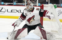 Arizona Coyotes goaltender Ivan Prosvetov avoids the puck as it aims for his head in the second period of an NHL hockey game against the Colorado Avalanche Monday, April 12, 2021, in Denver. (AP Photo/David Zalubowski)