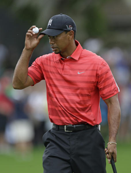 Tiger Woods tips his hat after sinking a putt on the first hole during the final round of the Arnold Palmer Invitational golf tournament Sunday March 24, 2013, in Orlando, Fla. (AP Photo/John Raoux)