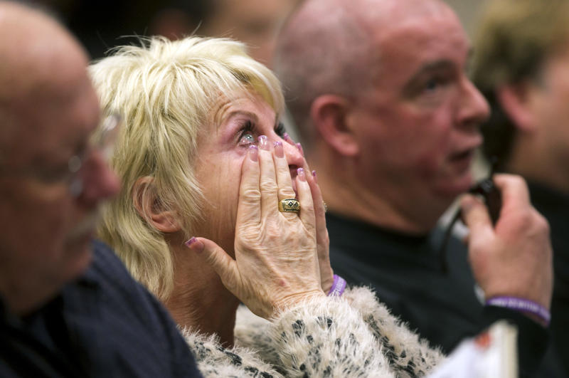 Shari Turbyfill, center, the wife of David Turbyfill, right, cries during the Industrial Commission of Arizona hearing on Wednesday, Dec. 4, 2013, in Phoenix. David's son and Shari's stepson, Travis Turbyfill, died fighting the Yarnell Hill Fire. The commission approved a nearly $560,000 fine on Wednesday against the state Forestry Division in the deaths of 19 firefighters after the Arizona Division of Occupational Safety and Health agency found that officials put protection of property ahead of safety and should have pulled out crews earlier. (AP Photo/The Arizona Republic, David Wallace)