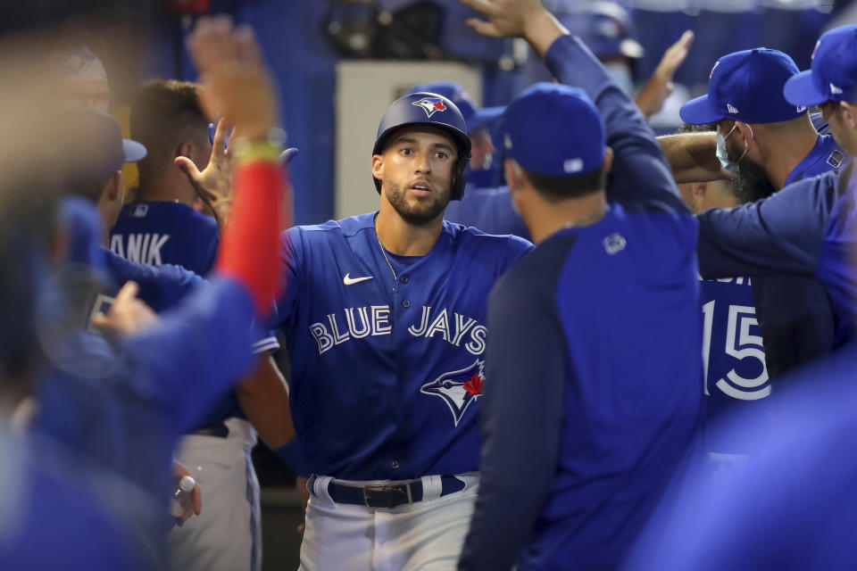 Toronto Blue Jays' George Springer is congratulated after his two-run home run against the Atlanta Braves during the third inning of a baseball game Saturday, May 1, 2021, in Dunedin, Fla. (AP Photo/Mike Carlson)