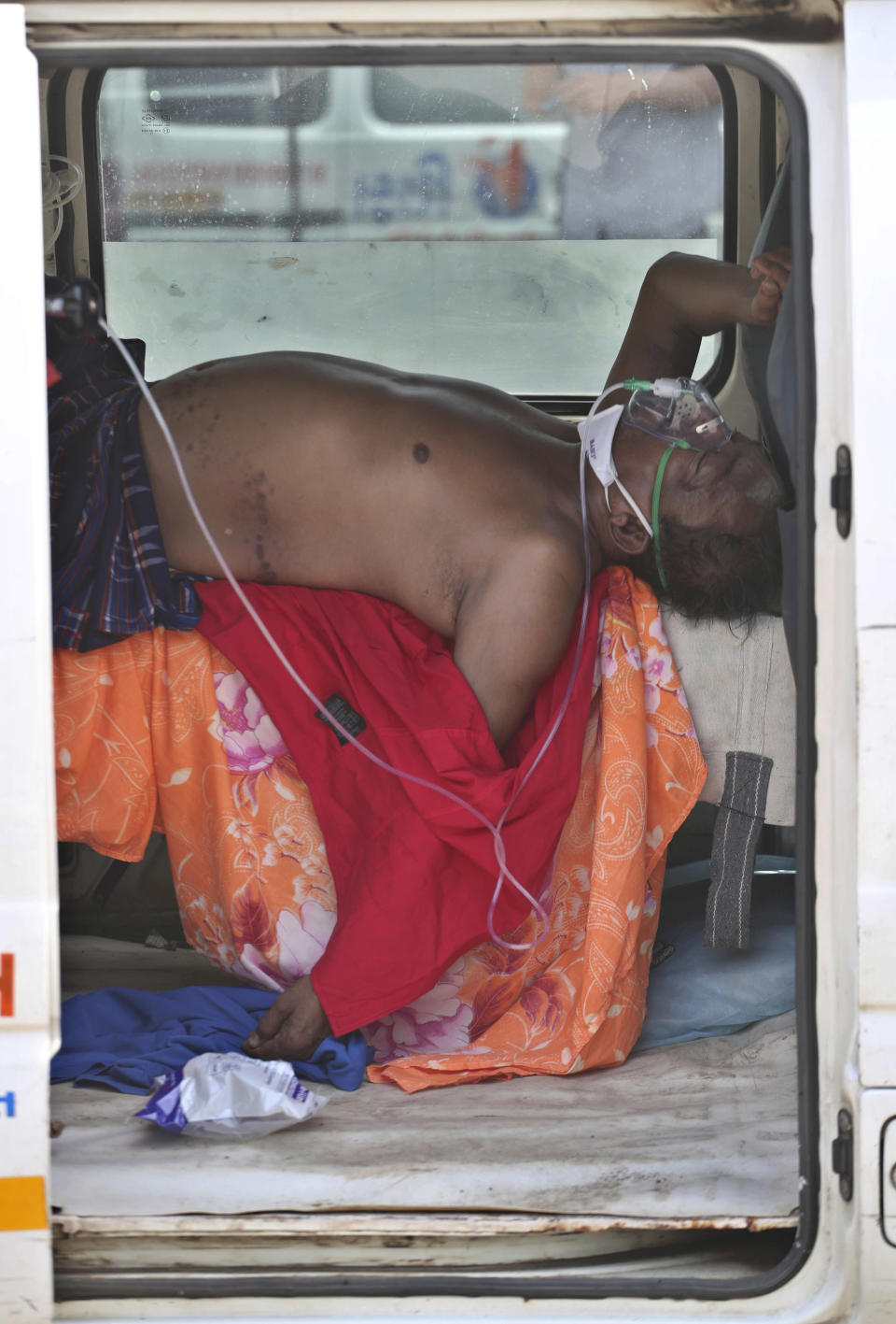 A COVID-19 patient lies inside a vehicle to be attended to and admitted in a dedicated COVID-19 government hospital in Ahmedabad, India, Thursday, April 22, 2021. India is putting oxygen tankers on special express trains as major hospitals in New Delhi begged on social media for more supplies to save COVID-19 patients who are struggling to breathe. Hospitals in New Delhi and some of the worst-hit states reported being critically short of beds and oxygen Saturday. (AP Photo/Ajit Solanki)