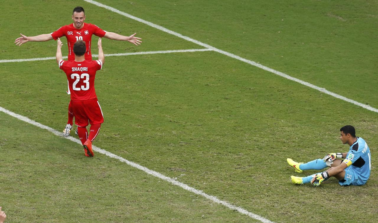 Switzerland's Xherdan Shaqiri (23) celebrates with a teammate after scoring against Honduras for his hat-trick during their 2014 World Cup Group E soccer match at the Amazonia arena in Manaus June 25, 2014. REUTERS/Andres Stapff (BRAZIL - Tags: SOCCER SPORT WORLD CUP)