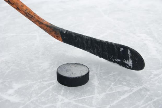 A hockey stick and puck are seen in this stock photo. There are concerns about the future of hockey at the Victoria Highland Civic Centre in Baddeck, N.S., after an engineer's report found a laundry list of issues, including a leaky roof and rusting beams.  (Shutterstock - image credit)