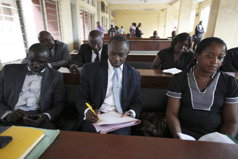 Lawyers representing victims of crash look through court documents during a ruling at the Magistrate court in Lagos, Nigeria, Wednesday, April. 25, 2012. The failures of Africa's most populous nation seemed to explode into a fiery multiple car and truck crash in Nigeria that killed at least 18 people in 2010, according to a coroner's ruling issued Wednesday. Police set up an illegal checkpoint August 2010 along a major expressway in Lagos, using tires to funnel traffic down to one lane as officers demanded bribes from motorists, witnesses said. The driver of a speeding truck carrying sugar for the nation's largest industrial company tried to stop, but the vehicle's bad brakes failed and the truck slammed into waiting traffic, witnesses and officials said. Those details, long denied by authorities, came out Wednesday when a coroner investigating the deaths ruled against Nigeria's federal police and the Dangote Group, owned by billionaire Aliko Dangote. (AP Photos/Sunday Alamba)