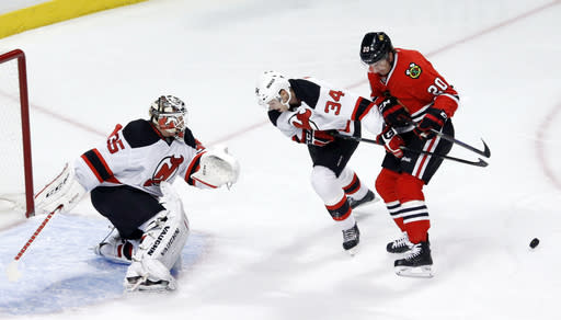 New Jersey Devils defenseman Jon Merrill (34) keeps Chicago Blackhawks left wing Brandon Saad from getting a rebound shot on Devils goalie Cory Schneider during the first period of an NHL hockey game Monday, Dec. 23, 2013, in Chicago. (AP Photo/Charles Rex Arbogast)