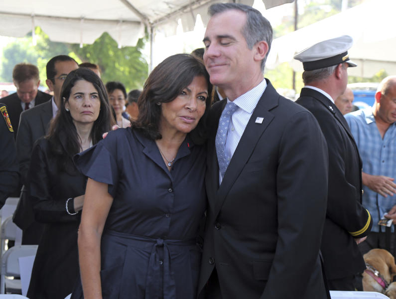 Paris Mayor Anne Hidalgo and Los Angeles Mayor Eric Garcetti share a moment following a ceremony marking the 17th anniversary of the Sept. 11, 2001 terrorist attacks on America, at the Los Angeles Fire Department's training center Tuesday, Sept. 11, 2018. Americans looked back on 9/11 Tuesday with tears and somber tributes. Victims' relatives said prayers for their country, pleaded for national unity and pressed officials not to use the 2001 terror attacks as a political tool in a polarized nation. (AP Photo/Reed Saxon)