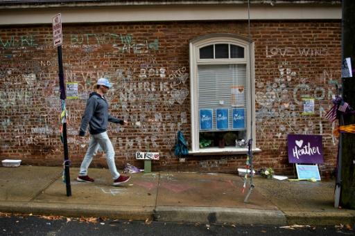 A man walks past a memorial to Heather Heyer and the other victims of a hit-and-run during a neo-Nazi rally in Charlottesville, Virginia