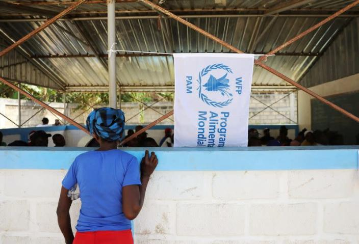 FILE PHOTO: A woman watches as money is distributed by the World Food Programme in Bainet