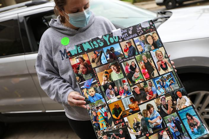 Jennifer Hair, 36, of Canton holds up a poster the family made of pictures of them together to help motivate her mother, Deanna Hair as she battled COVID-19 at the University of Michigan hospital for 196 days.