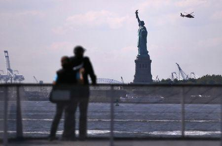Tourists pause to view the Statue of Liberty from a Liberty Island ferry boat at Battery Park in New York