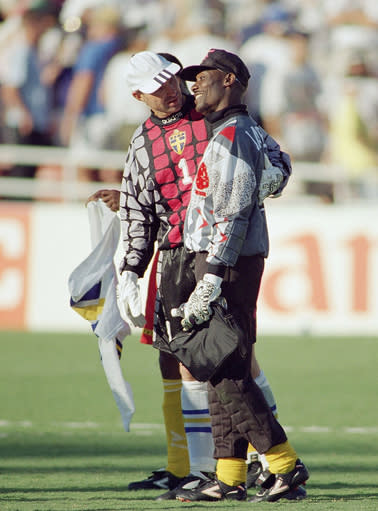 FILE - In this file photo dated Sunday, June 19, 1994, Goalkeeper Thomas Ravelli of Sweden, left, and Joseph-Antoine Bell of Cameroon hug each other as they walk out of the field after the 2-2 tie of the Sweden Vs Cameroon Group B first round match of the World Cup soccer championship at the Rose Bowl in Pasadena, USA. The extrovert Sweden goalkeeper Ravelli who helped give the Scandinavian nation one of its greatest sporting rushes when the Sweden team reached the semifinals of the 1994 World Cup in the United States, and Sweden's national TV broadcaster plans to replay the team's games over the coming weeks in an attempt to unite the nation during the coronavirus pandemic. (AP Photo/Lois Bernstein, File)