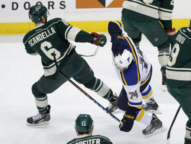 St. Louis Blues right wing T.J. Oshie (74) gets an illegal check to the head from Minnesota Wild defenseman Marco Scandella (6) during the first period of an NHL hockey game in St. Paul, Minn., Saturday, Nov. 29, 2014. Scandella was charged with a minor penalty on the play. (AP Photo/Ann Heisenfelt)