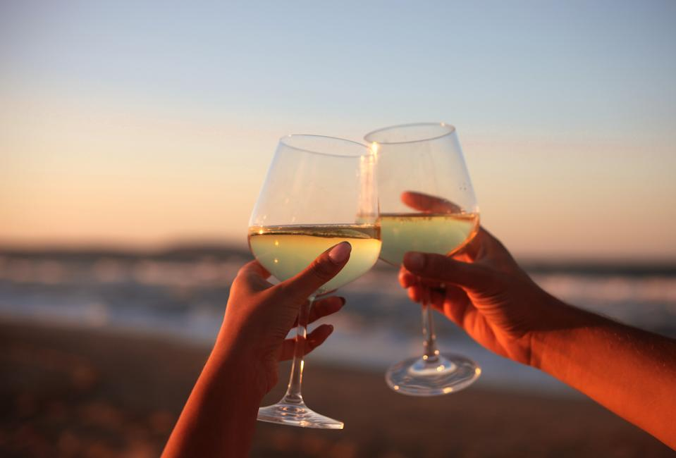 Male and female hands holding wine glasses in hands on the summer beach in sunset. Romantic concept of love, couple, wedding and vacation.