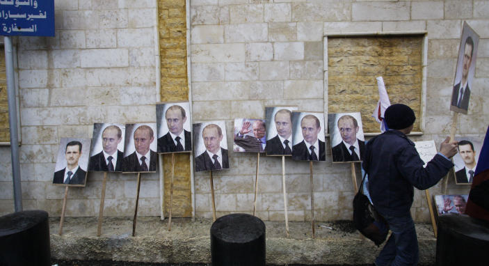 FILE - In this Sunday, March 4, 2013 file photo, photos of Syrian President Bashar Assad and Russian Prime Minister Vladimir Putin are propped against a wall during a pro-Syrian regime protest in front of the Russian embassy in Damascus. In a few days' worth of opportunistic diplomacy, Vladimir Putin has revived memories of an era many thought long gone, where the United States and Soviet Union jostled for influence in a Middle East torn between two powers. Whatever happens with its proposal to relieve Syria of chemical weapons, Russia reemerges as a player in the region _ and one who does not easily abandon allies. That's meaningful in a region where America's dumping of Hosni Mubarak has emerged as a seminal moment _ and it may resonate with Iran, whose leaders are carefully watching the global chessboard as the clock ticks toward another showdown, over their nuclear program. (AP Photo/Muzaffar Salman, File)