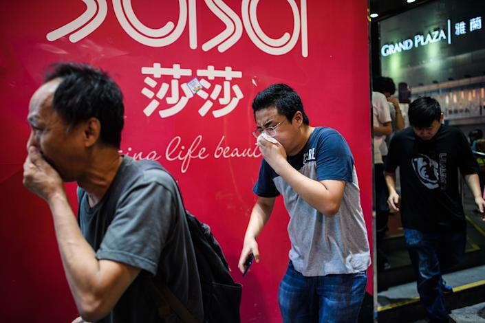 Bystanders react after police fired tear gas to disperse residents and protesters in the Mong Kok district of Kowloon in Hong Kong on October 27, 2019. | ANTHONY WALLACE—AFP via Getty Images