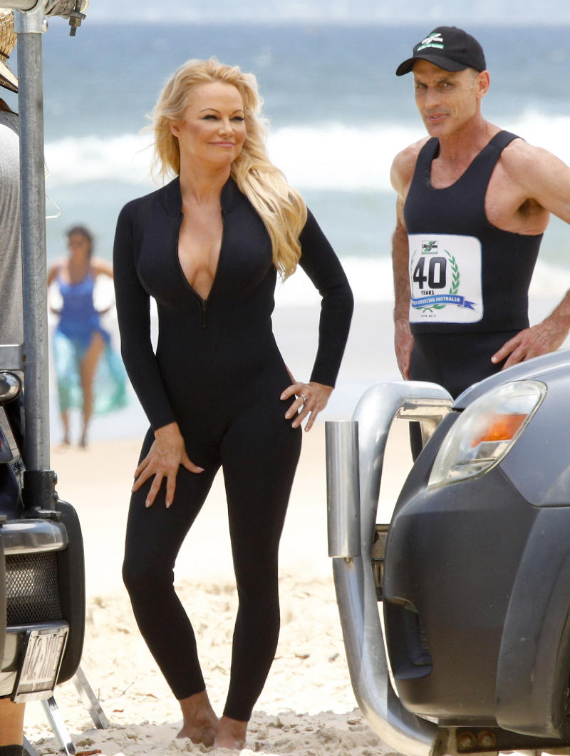 Pamela Anderson poses in a black wetsuit unzipped on set the Ultratune set on Gold Coast beach