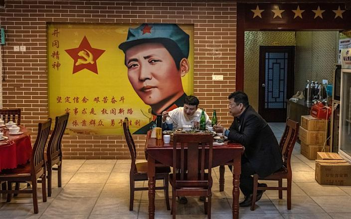 People eat under the watchful gaze of former Chinese leader Mao Zedong in a restaurant in Jinggangshan, a historically important area where the Communist Party found its first rural base in 1927 - ROMAN PILIPEY/EPA-EFE/Shutterstock