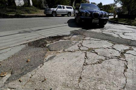 A pothole is pictured on the street of Los Angeles, California February 12, 2016. Nearly two-thirds of Americans would support roadway user fees to help fix the country's crumbling transportation infrastructure, according to a survey to be published on April 28, 2016 that was seen by Reuters.      REUTERS/Mario Anzuoni/File Photo