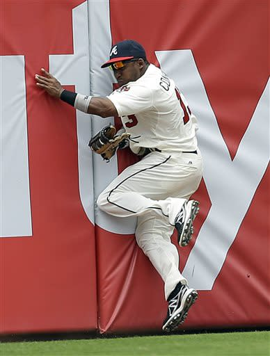 Atlanta Braves left fielder Jose Canstanza crashes into the wall after making a catch to retire Cincinnati Reds' Shin-Soo Choo in the first inning of a baseball game on Sunday, July 14, 2013, in Atlanta. (AP Photo/John Bazemore)