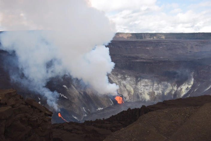 In this photo provided by the U.S. Geological Survey, plumes rise from active fissures in the crater of Hawaii's Kilauea volcano on Tuesday, Dec. 22, 2020. Lava is rising more than 3 feet per hour in the deep crater of a Hawaii volcano that began erupting over the weekend. The U.S. Geological Survey says Kilauea volcano within Hawaii Volcanoes National Park on the Big Island was gushing molten rock from at least two vents inside its summit crater. (U.S. Geological Survey via AP)