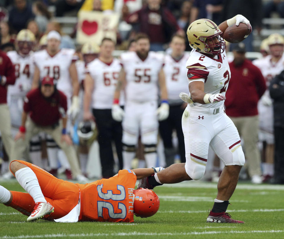 Boston College running back AJ Dillon (2) breaks a tackle by Boise State safety Jordan Happle (32) on a touchdown run during the first half of the First Responder Bowl NCAA football game Wednesday, Dec. 26, 2018, in Dallas. (AP Photo/Richard W. Rodriguez)