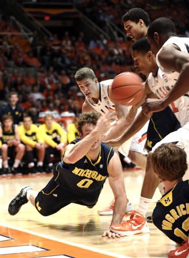 Michigan guard Zack Novak (0) dives for a ball along the baseline against Illinois in the first half of an NCAA college basketball game in Champaign, Ill., on Thursday, March 1, 2012. (AP Photo/John Dixon)