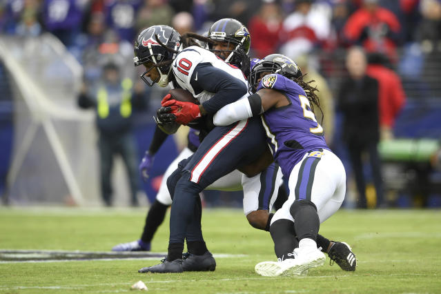 Houston Texans wide receiver DeAndre Hopkins (10) is tackled by Baltimore Ravens middle linebacker Josh Bynes, right, and cornerback Marcus Peters during the first half of an NFL football game, Sunday, Nov. 17, 2019, in Baltimore. (AP Photo/Nick Wass)