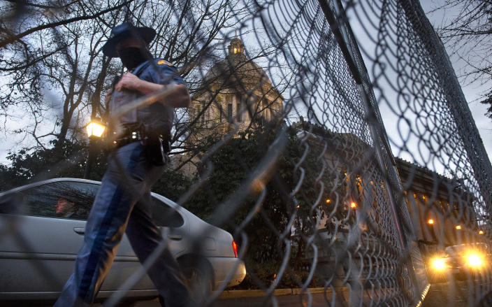 A Washington State Patrol trooper walks past new security fencing installed on Friday, Jan. 8, 2021, around the state Capitol in Olympia, Wash.. in anticipation of the legislative session opening on Monday. (Tony Overman/The Olympian via AP)