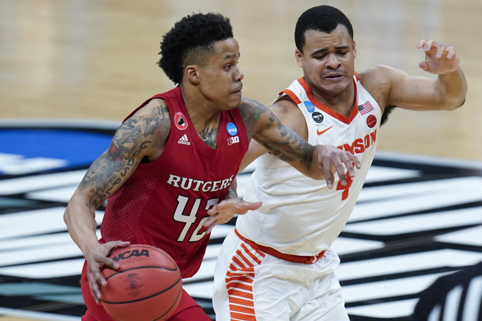 Clemson guard Nick Honor (4) defends Rutgers guard Jacob Young (42) during the second half of a men's college basketball game in the first round of the NCAA tournament at Bankers Life Fieldhouse in Indianapolis, Friday, March 19, 2021. (AP Photo/Paul Sancya)