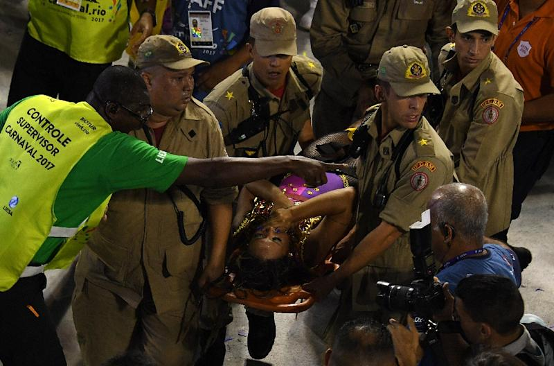 Firefighters assist a reveller of the Unidos da Tijuca samba school at the Sambadrome in Rio de Janeiro early on February 28, 2017, after the third floor of an allegorical car collapsed during the second night of Rio Carnival (AFP Photo/Vanderlei Almeida)