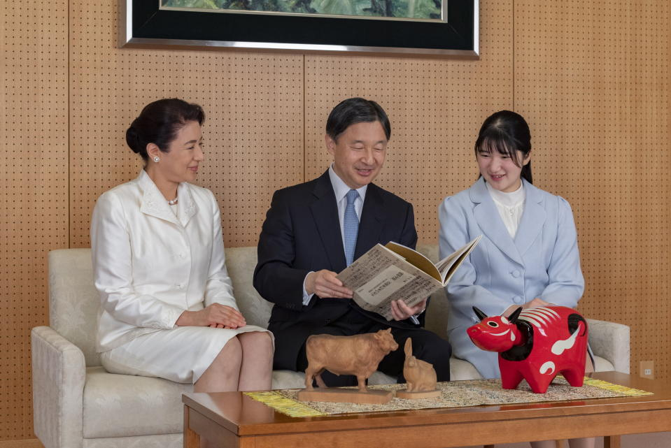 In this photo provided by the Imperial Household Agency of Japan, Japan's Emperor Naruhito, center, talks with her wife Empress Masako, left, and their daughter Princess Aiko during a family photo session for the New Year at their Akasaka Estate residence in Tokyo, in Tokyo, on Dec. 21, 2020. (The Imperial Household Agency of Japan via AP)
