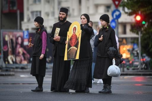 A Christian-Orthodox family holds an icon during a protest against the 'sanitary dictatorship'