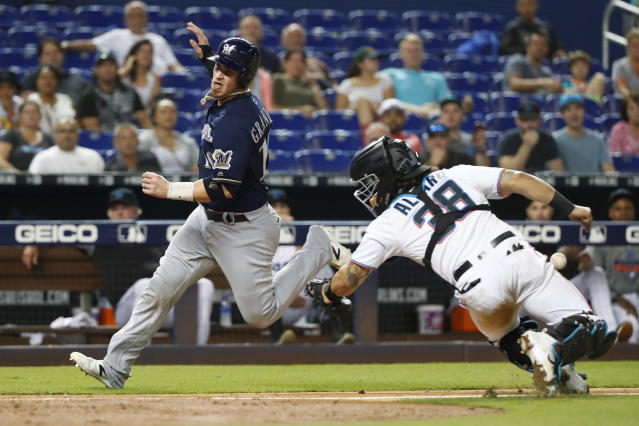 Milwaukee Brewers' Yasmani Grandal (10) heads for home plate to score on a sacrifice fly by Tyler Austin as Miami Marlins catcher Jorge Alfaro (38) attempts the tag during the ninth inning of a baseball game Tuesday, Sept. 10, 2019, in Miami. The Brewers defeated the Marlins 4-3. (AP Photo/Wilfredo Lee)