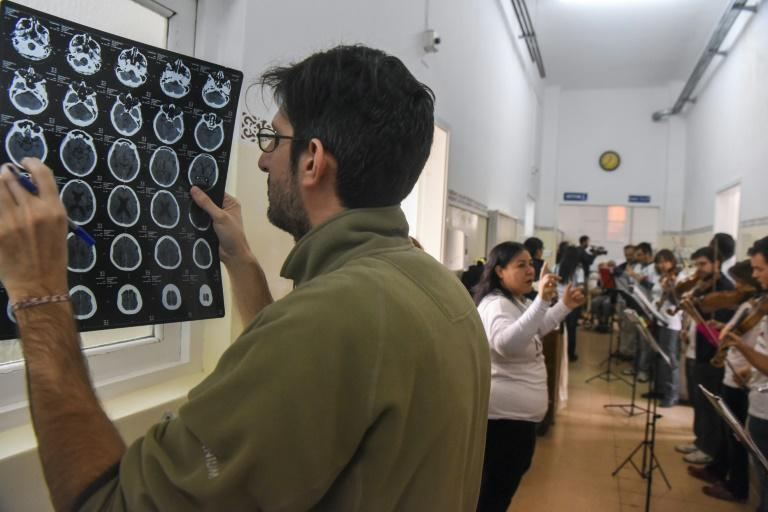 A doctor looks at a cat-scan as volunteer members of Musica Para el Alma (Music for the Soul) perform for patients at the Alvarez Hospital in Buenos Aires in June