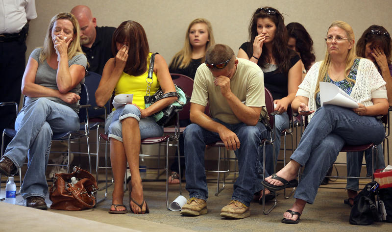 Family members of Britny Haarup, 19, and Ashley Key, 22, react during a press conference regarding their murder Monday morning July 16, 2012, at the Platte County Resource Center in Kansas City, Mo. Clifford D. Miller was charged Monday with two counts of first-degree murder in the deaths of the two sisters in Edgerton, Mo. (AP Photo/St. Joseph News-Press, Eric Keith)