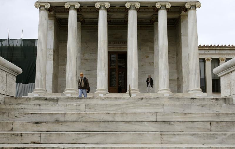 Pedestrians walk past the Academy of Athens, Tuesday, Dec. 17, 2013. Greece's central bank has joined the government in predicting that the country's economy will grow in 2014 following a savage six-year recession but cautioned about the impact of a heated political rivalry ahead of elections in May. (AP Photo/Thanassis Stavrakis)