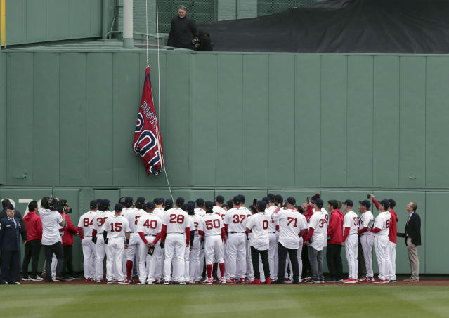 The Boston Red Sox team gathers as the 2018 World Series Champions pennant is hoisted in center field before the home opener baseball game between the Red Sox and the Toronto Blue Jays, Tuesday, April 9, 2019, in Boston. (AP Photo/Charles Krupa)