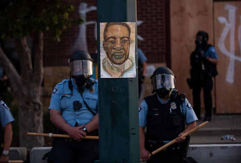 A portrait of George Floyd hangs on a street light pole as police officers stand guard at the Third Police Precinct during a face off with a group of protesters in Minn., Minnesota, May 27, 2020. | Stephen Maturen—Getty Images