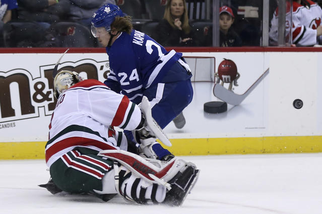 New Jersey Devils goaltender Keith Kinkaid clears the puck past Toronto Maple Leafs right wing Kasperi Kapanen (24) during the first period of an NHL hockey game Thursday, Jan. 10, 2019, in Newark, N.J. (AP Photo/Adam Hunger)