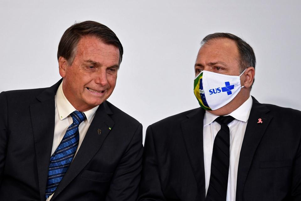 Brazilian President Jair Bolsonaro (L) and Brazilian Health Minister Eduardo Pazuello attend a ceremony to launch the Genomas Project at Planalto Palace in Brasilia on October 14, 2020. - The Genomas Project aims at making a population study to identify rare diseases by sequencing the DNA of 100,000 Brazilians. (Photo by EVARISTO SA / AFP) (Photo by EVARISTO SA/AFP via Getty Images)