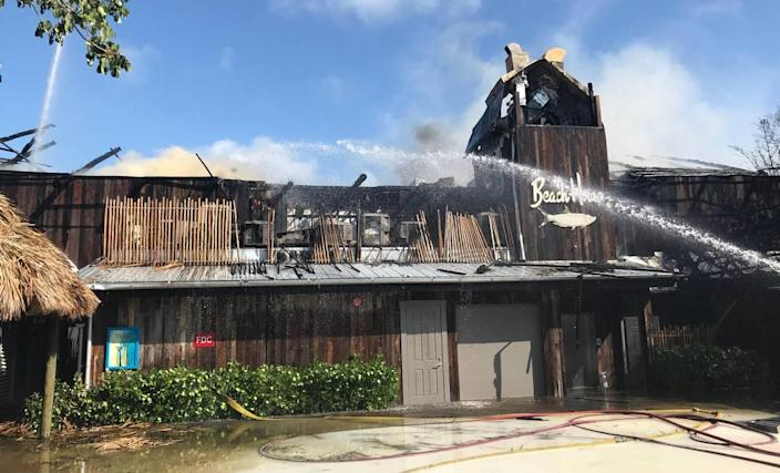 Key Largo Volunteer Fire Department firefighters spray a hose on the smoldering facade of Bungalows Key Largo, a resort that caught fire May 5, 2019. The fire was so strong that the tiki-style roof continued to smoulder almost two days after firefighters knocked down the flames.