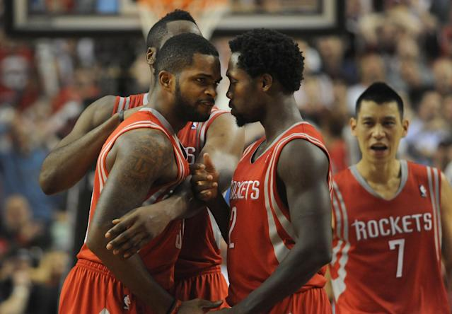 PORTLAND, OR - APRIL 25: Troy Daniels #30 of the Houston Rockets is mobbed by teammates James Harden #13 and Patrick Beverley #2 after hitting what ended up to be the game winning shot during overtime of Game Three of the Western Conference Quarterfinals during the 2014 NBA Playoffs against the Portland Trail Blazers at the Moda Center on April 25, 2014 in Portland, Oregon. The Rockets won the game 121-116. NOTE TO USER: User expressly acknowledges and agrees that, by downloading and or using this photograph, User is consenting to the terms and conditions of the Getty Images License Agreement. (Photo by Steve Dykes/Getty Images)