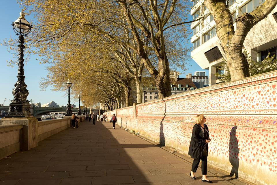 People pay tributes by painting hearts and signatures on the wall as the city re-opens after COVID cases subside. The National COVID Memorial Wall is established along the banks of River Thames, outside St. Thomas' Hospital in London to commemorate NHS staff and patients who have given their lives over the course of the Pandemic. (Photo by Belinda Jiao / SOPA Images/Sipa USA)