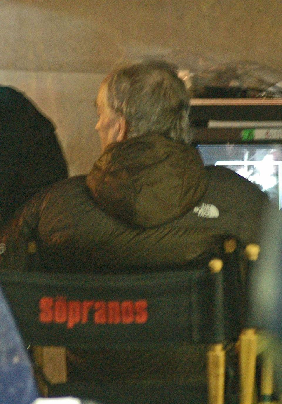 <p>David Chase sits in the producer's chair to review a scene while filming in New York City's Chinatown. </p>