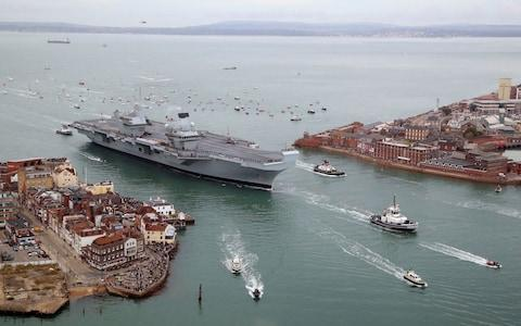 A flotilla of craft follow HMS Queen Elizabeth as she sails into Portsmouth Harbour - Credit: Gareth Fuller/PA
