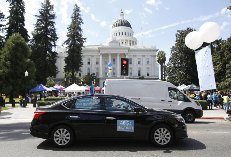 FILE - In this Aug. 28, 2019, file photo, dozens of supporters of a measure to limit when companies can label workers as independent contractors circle the Capitol during a rally in Sacramento, Calif. Gov Gavin Newsom signed the bill AB5 by Assemblywoman Lorena Gonzalez, D-San Diego, aimed at giving wage and benefit protections to ride share drivers and workers in other industries on Wednesday, Sept. 18, 2019. (AP Photo/Rich Pedroncelli, File)